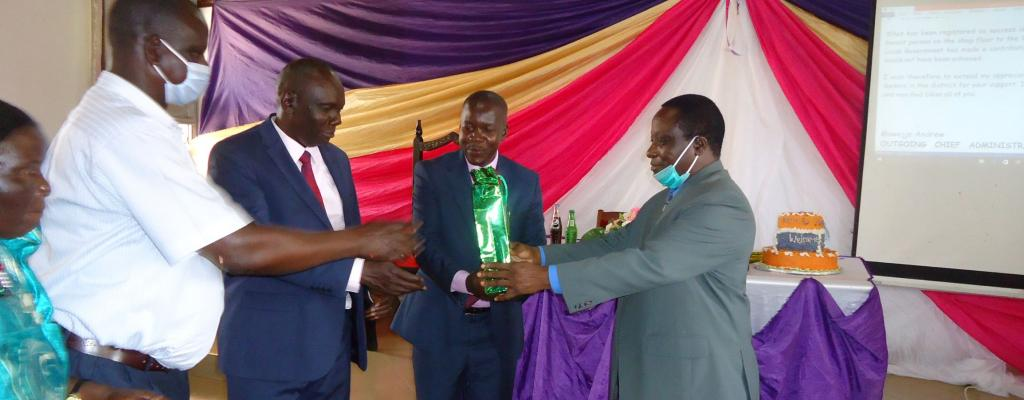 CAO Mawejje Andrew Hands over a gift to RDC and elected Leadership